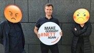 Ein Mann hält ein rundes Schild in den Händen: Make Germany nett again. Deneben stehen zwei Menschen mit negativen Smileys vor den Gesichtern. © NDR/Kulturjournal Fotograf: Stefan Mühlenhoff