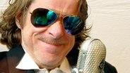 Helge Schneider mit Spiegelbrille vor Mikrofon © Helge Schneider Enterprises / Till Oellerking