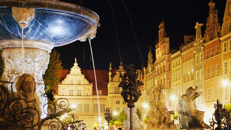 Der Lange Markt bei Nacht. Ein blauer Brunnen steht in der linken Ecke vor historischen Häusern. © NDR/MoersMedia/Peter Moers