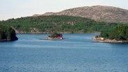 Ein rotes Haus auf einer Insel in Schären in Norwegen. © NDR Foto: Wolfgang Fromm