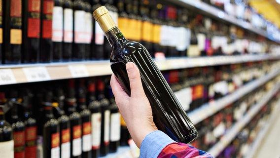 Rotweinflasche wird aus einem Regal im Supermarkt genommen © Fotolia.com Fotograf: Sergey Ryzhov