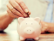 Sparschwein wird mit Münze befüllt. © Fotolia.com Foto: Syda Productions
