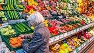 Eine Kundin packt in einem Lebensmittelmarkt frisches Gemüse in einen Einkaufskorb. © picture alliance / ZB Foto: Jens Büttner