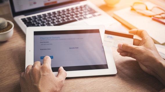 Mann hält Kreditkarte und tippt Daten online mit Tablet ein. © Fotolia Foto: Mymemo