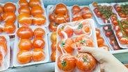 Eine Hand greift ein Packet mit verpackten Tomaten. © fotolia Fotograf: petunyia