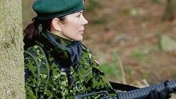 Mit dem Gewehr im Anschlag geht Prinzessin Mary in einem Wald in Deckung. © dpa