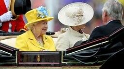 Zusammen mit Prinzessin Anne fährt die Queen in einer offenen Kutsche zur Eröffnung des Pferderennens Royal Ascot. © Picture-Alliance / Empics