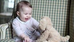 Prinzessin Charlotte lacht einen Stoffhund an. © dpa-Bildfunk Fotograf: The Duchess of Cambridge