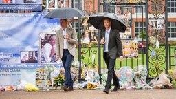 Prinz William und Prinz Harry schauen sich die Blumen und Trauersprüche an, die Passanten zum 20. Todestag von Diana am Kensington Palace niedergelegt haben. © Picture-Alliance / Photoshot