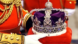 Ein Diener trägt die britische Königskrone zur Parlamentseröffnung © Picture-Alliance / dpa