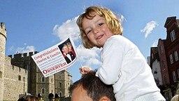 9. April 2005: Am Hochzeitstag von Camilla und Charles sitzt ein kleines Mädchen auf den Schultern ihres Vaters und hat eine Fahne in der Hand © Picture-Alliance / dpa Fotograf: Fiona Hanson