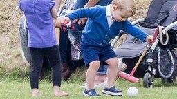 Prinz George spielt mit Ball und Schläger am Rand eines Polo-Turniers in Tetbury. © Picture-Alliance / Zuma Press