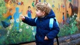 Prinz George zeigt an seinem ersten Tag im Kindergarten auf eine bunt bemalte Wand. © dpa-Bildfunk