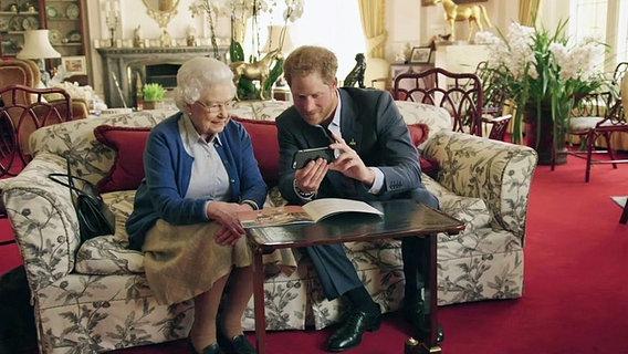 Prinz Harry zeigt Queen Elizabeth II. eine Nachricht auf seinem Smartphone. © dpa Fotograf: Royal Household / Kensington Palace