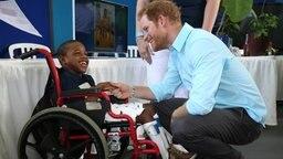 Prinz Harry begrüßt ein Kind im Rollstuhl bei seinem Besuch auf der Karibik-Insel St. Lucia.  © picture alliance / empics Fotograf: Chris Radburn