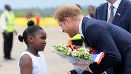 Der britische Prinz Harry erhält Blumen von einem afrikanischen Mädchen bei seiner Ankunft am Flughafen in Lusaka. Prinz Harry ist für einen kurzen Staatsbesuch in Sambia. ©  Tsvangirayi Mukwazhi/AP/dpa Foto:  Tsvangirayi Mukwazhi
