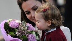 Herzogin Kate mit Tochter Prinzessin Charlotte, die an einem Blumenstrauß riecht © dpa Picture Alliance Fotograf: Royalfoto