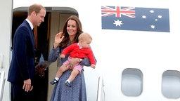 Prinz William und Herzogin Kate mit Baby George stehen in Australien auf der Gangway eines Flugzeuges und verabschieden sich. © dpa-Bildfunk Fotograf: Alan Porritt