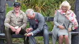 Prince Charles und Camilla sitzen auf eine Bank und lachen, weil Charles eine agile kleine Echse in der Hand hält. © picture-alliance/Schwörer Pressefoto Fotograf: Kai Schwörer