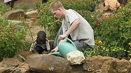 Prinz Harry pflanzt zusammen mit einem afrikanischen Kind aus Lesotho einen Baum ein © picture alliance / AP Photo Fotograf: Ben Curtis