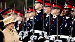 Queen Elizabeth II. steht am 12. April 2006 bei der Abschlussparade in Sandhurst dem lächelnden Prinz Harry und weiteren Rekruten gegenüber © picture-alliance / dpa Fotograf: Dylan Martinez