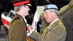 Lächelnd nimmt Prinz Harry am 7. Mai 2010 das zur bestandenen Pilotenausbildung gehörende Abzeichen von seinem Vater, Prinz Charles, entgegen. © picture alliance / dpa