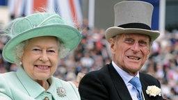 Königin Elizabeth II. und ihr Ehemann Prinz Philip fahren mit einer Kutsche beim Royal Ascot Ladies Day vor. © dpa