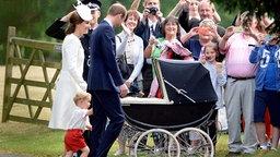Prinz William hat seinen Sohn George an der Hand, Herzogin Kate schiebt einen Kinderwagen. © picture alliance Fotograf: Andrew Parsons
