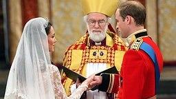 Prinz William hält die Hand von Kate Middleton am 29. April 2011 am Traualtar in Westminster Abbey im Beisein des Erzbischofs von Canterbury. © picture alliance / empics