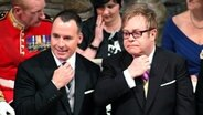 Elton John (rechts) und sein Partner David Furnish (hinten) am 29. April 2011 in der Westminster Abbey. © picture alliance / empics