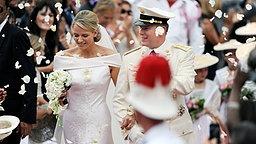 Fürstin Charlene Grimaldi und Fürst Albert II. gehen am 2. Juli 2011 nach der Trauungszeremonie auf dem Palastplatz in Monte Carlo durch einen Rosenregen. © dpa-Bildfunk