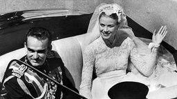 Rainier und Grace Kelly im offenen Hochzeitswagen. Am 19. April 1956 heiratet der Fürst die amerikanische Filmschauspielerin. © dpa - Fotoreport Foto: UPI