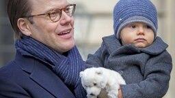 Feierlichkeiten zu Victorias Namenstag in Schweden: Prinz Daniel  trägt Prinz Oscar auf dem Arm. © dpa Fotograf: Patrick van Katwijk
