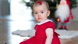 Prinzessin Estelle sitzt vor einem Weihnachtsbaum in einem roten Kleid.  © Kungahuset.se Foto: Kate Gabor