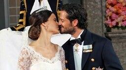 Prinz Carl Philip und Sofia geben sich einen Hochzeitskuss. ©  picture alliance/IBL Schweden Fotograf: Charles Hammarsten / IBL Bildbyrå