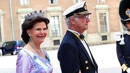 Königin Silvia und König Carl Gustaf von Schweden gehen über den roten Teppich vor der Kapelle des Königspalastes in Stockholm. © dpa - Bildfunk