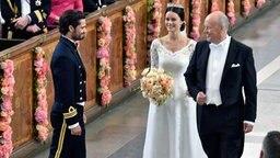 Sofias Vater Erik Hellqvist übergibt seine Tochter in der Kapelle des Stockholmer Palasts an Prinz Carl Philip. © dpa - Bildfunk/EPA Fotograf: Jonas EkstroemerTt