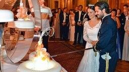 Prinz Carl Philip und seine Frau Sofia schneiden die Hochzeitstorte an. © dpa-Bildfunk Fotograf: Anders Wiklund