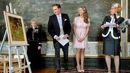Christopher O'Neill und Prinzessin Madeleine blicken mit der gotländischen Gouverneurin Gotland Cecilia Schelin Seidegard auf ein Pferdebild, © dpa-Bildfunk Fotograf: Jessica Gow
