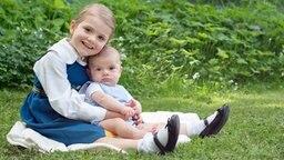 Die schwedische Prinzessin Estelle und der kleine Prinz Oscar sitzen am Nationalfeiertag auf einer Wiese - ein Aufnahme vom 6. Juni 2016. © Kungahuset.se Foto: Kate Gabor