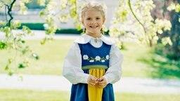 Prinzessin Estelle steht in schwedischer Tracht auf einer Wiese. © The Royal Court, Sweden Foto: Erika Gerdemark