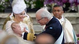 Kronprinzessin Victoria zeigt Prinz Oscar während seiner Taufe Großvater König Carl Gustaf. © dpa Bildfunk Fotograf: Pontus Lundahl