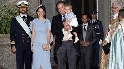 Prinz Carl Philip, Prinzessin Sofia und Christopher O'Neill - mit Prinz Nicolas auf dem Arm - posieren bei Prinz Oscars Taufe für Fotografen. © Picture-Alliance / dpa Fotograf: Albert Nieboer