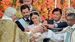 Sofia hält ihren Sohn Alexander im Arm während Erzbischöfin Antje Jaeckelen, Car Philip und die Paten ihre Hand über ihn halten. © dpa-Bildfunk Fotograf: Jonas Ekstromer