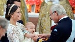 Prinzessin Sofia hält Prinz Alexander seinem Großvater Carl Gustaf entgegen. © dpa-Bildfunk Fotograf: Claudio Bresciani