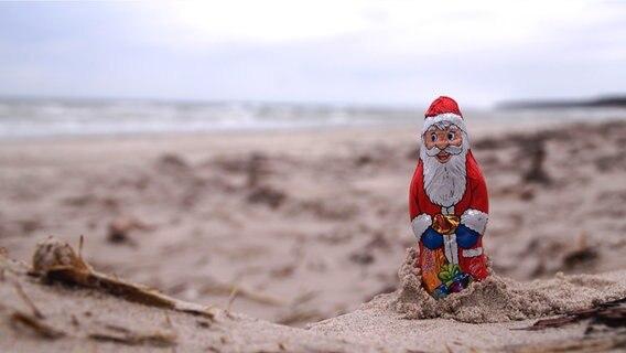 Ein Schoko-Weihnachtsmann steht im Sand am Strand. © NDR Foto: Sabine Schellbach aus Sachsen
