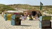 Ein Mann baut Liegestühle an einer Strandbar auf. © NDR