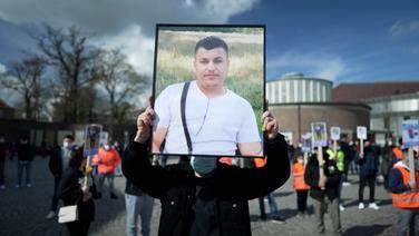 Eine Person hält ein Bild des verstorbenen Qosay K. in den Händen
