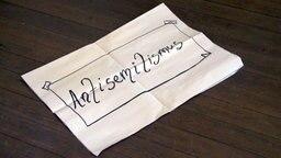 """Zettel mit der Aufschrift """"Antisemitismus"""" liegt auf auf einem Holffußboden. © NDR Foto: Screenshot"""
