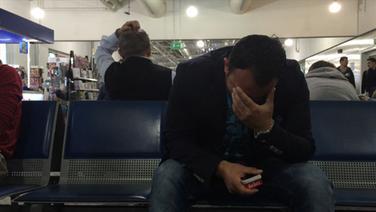 Rami wartet am Flughafen und hält sich die Hand vor sein Gesicht. © NDR Foto: NDR